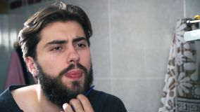 Young man comb his beard and moustache. Close-up of the guy.  stock footage