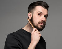 Young man comb his beard and moustache. On gray background Royalty Free Stock Photo