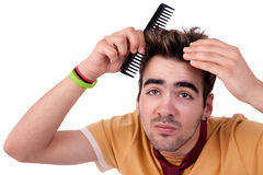 Young man combing his hair with a comb Royalty Free Stock Photos