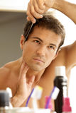 Young man combing his hair Stock Photo