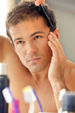 Young man combing his hair Stock Images