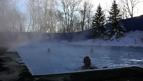 A young man comes to the land after swimming in the pool in the thermal waters in the cold winter snow day.  stock video footage