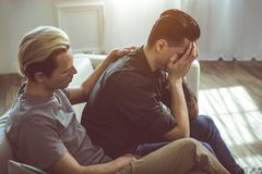 Young man comforting boyfriend while he covering face with arms stock photography