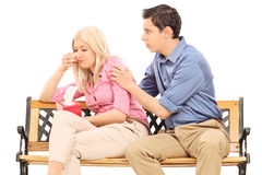 Young man comforting his sad girlfriend. Young men comforting his sad girlfriend isolated on white background stock photography
