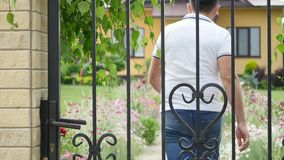 Young man coming home, opening, closing gate, yard, summer