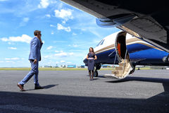 Young man coming to his jet with a welcoming air hostess air hostess Royalty Free Stock Photography