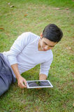 Young man communicate on social networks with tablet computer in Royalty Free Stock Images