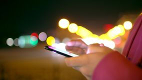 A young man is commuting to work while browsing his cellphone on a busy urban street at night. 4 k stock video