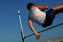 Young man competing in high jump. Boy clearing the high jump bar in a track and field competition Stock Photos