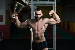 Young Man Competitor Showing His Winning Medal. Bodybuilder Competitor Showing His Winning Medal - Male Fitness Competitor Showing His Winning Medal Royalty Free Stock Photography
