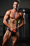 Young Man Competitor Showing His Winning Medal. Bodybuilder Competitor Showing His Winning Medal - Male Fitness Competitor Showing His Winning Medal Stock Image