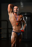 Young Man Competitor Showing His Winning Medal. Bodybuilder Competitor Showing His Winning Medal - Male Fitness Competitor Showing His Winning Medal Stock Photo