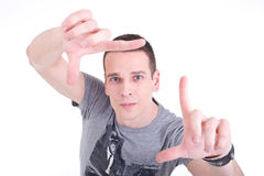 Young man composes with his hands. While looking at camera. Studio shot Stock Images