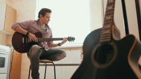 Young man composes music on the guitar and plays in the kitchen, other musical instrument in the foreground,. Young man composes music on the guitar and play in stock video