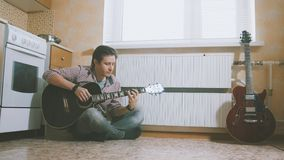 Young man composes music on the guitar and plays in the kitchen, other musical instrument in the foreground,. Young man composes music on the guitar and play in Royalty Free Stock Images