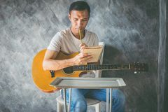 Music composing. Young man composing the song with guitar on table stock photo
