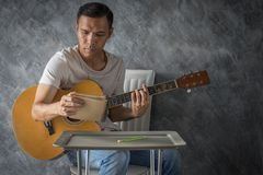 Music composing. Young man composing the song with guitar on table royalty free stock image