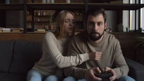 Young man concentrated on playing video games. Addicted. Young bearded man playing video games and expressing attention while his girlfriend bothering him stock footage