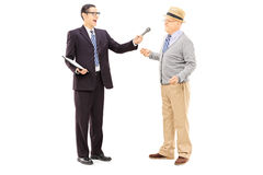 Young man conducting survey on middle aged man with microphone i Royalty Free Stock Images