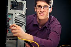 Young Man Connecting Network Cable. Young man connecting a network cable stock images