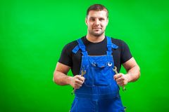 Dark-haired male construction. A young man construction  builder in a black T-shirt and blue construction overall holds in his hands a new tool combination Royalty Free Stock Photo