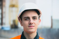 Young man in construction in orange vest royalty free stock image