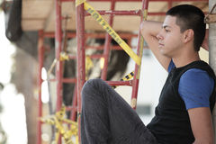 Young man by a construction site Royalty Free Stock Image