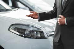 Car sales. Young man consultant in showroom is standing near car royalty free stock images