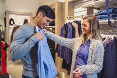 Young man consults with girlfriend while selecting a shirt. Young men consults with girlfriend while selecting a shirt in store stock image