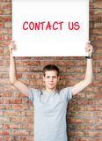 Young man with contact us words Stock Photos