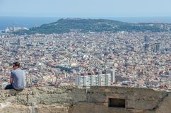 Young man contemplates the city. Of Barcelona from the Carmel on a day of June 2016 Royalty Free Stock Photo