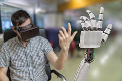 Young man is controlling robotic hand with virtual reality headset Stock Photos