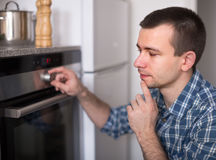 Young man controls the oven in the kitchen Stock Photography
