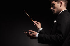 Young man contuctig an orchestra. Royalty Free Stock Photos