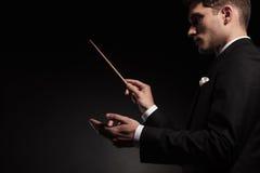 Young man contuctig an orchestra. Royalty Free Stock Photos
