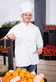 Young man cook deciding on best fruits Royalty Free Stock Photos