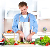 Young Man Cooking. Healthy Food - Vegetable Salad Royalty Free Stock Photography