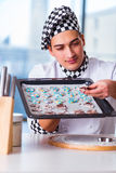 The young man cooking cookies in kitchen Royalty Free Stock Photography
