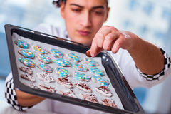 The young man cooking cookies in kitchen Royalty Free Stock Photo