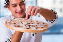 The young man cooking cookies in kitchen Royalty Free Stock Image