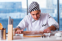The young man cooking cookies in kitchen Stock Photography
