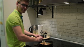 Young man cooking dinner in home kitchen stock footage