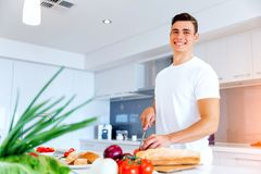 Young man cooking royalty free stock photography