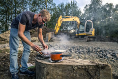 Young man is cooking sausages in the front of the construction Royalty Free Stock Photos