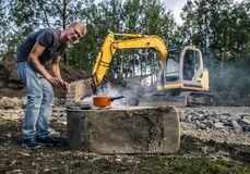 Young man is cooking sausages in the front of the construction Royalty Free Stock Photography