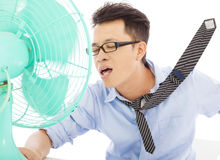 Young man cooling face under wind of fan. Summer heat Royalty Free Stock Image