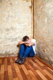 Sad Young Man. Young Man in the Corner on the Floor by the Old Wall stock photography