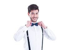 Young man correcting his bow tie, smiling. Isolated on white bac Royalty Free Stock Photo