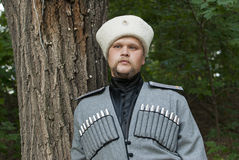 Young man in a cossack clothes in a forest. This image has attached release Stock Photos