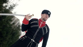 A young man in Cossack clothes swinging a sword in a winter landscape in the snow. stock video